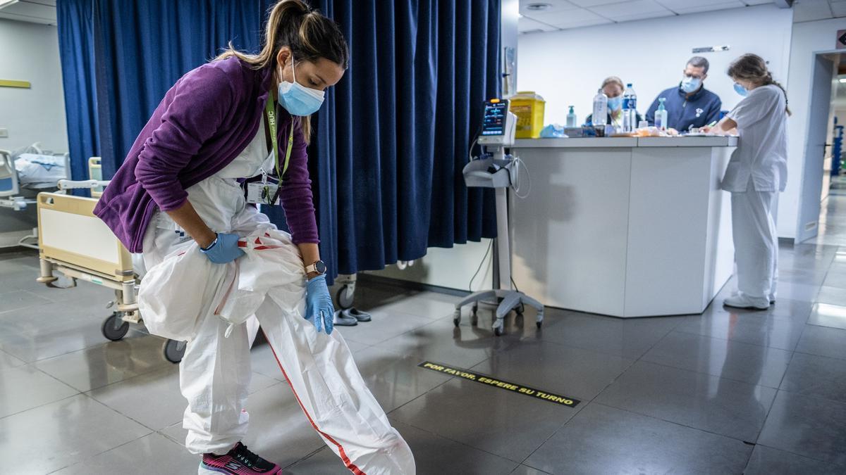 Una sanitaria se prepara para atender a un paciente con Covid.