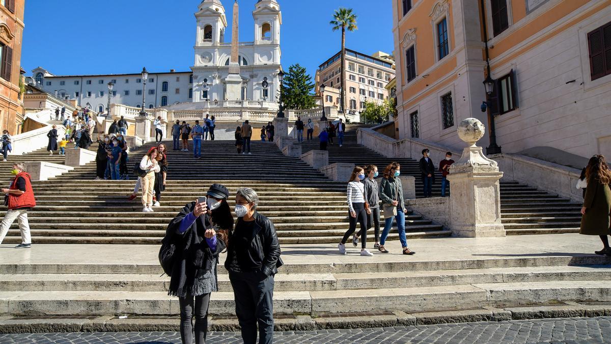 Turistas con mascarilla en la Plaza de España de Roma.