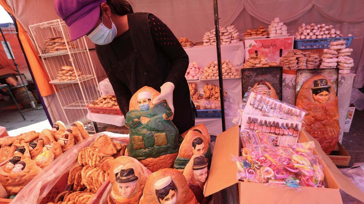 Una vendedora con panes que representan enfermeras y médicos con mascarilla.
