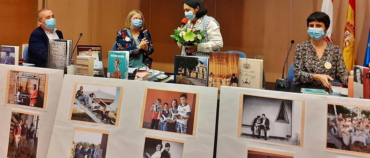 La bibliotecaria Carmen Dintén recibe de la concejala Cecilia Tascón un ramo de flores como obsequio por el décimo cumpleaños del club. | B. G.
