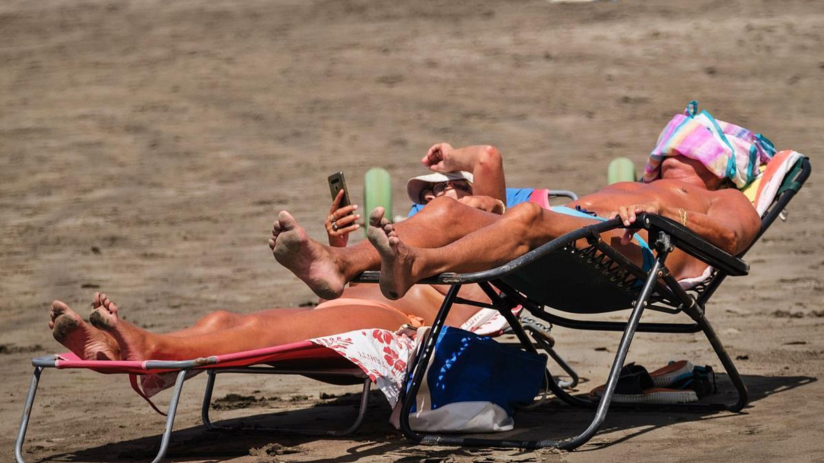 Dos turistas toman sol en la playa de Los Cristianos.