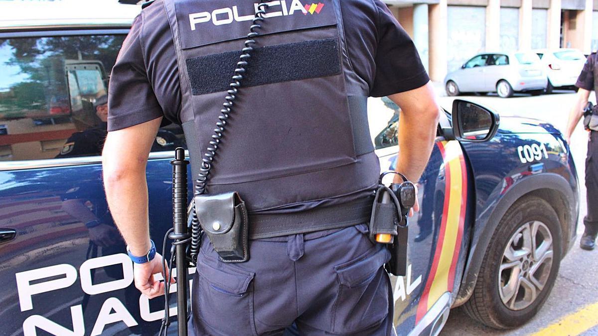 Imagen de archivo de dos agentes y un vehículo de la Policía Nacional. | LEVANTE-EMV