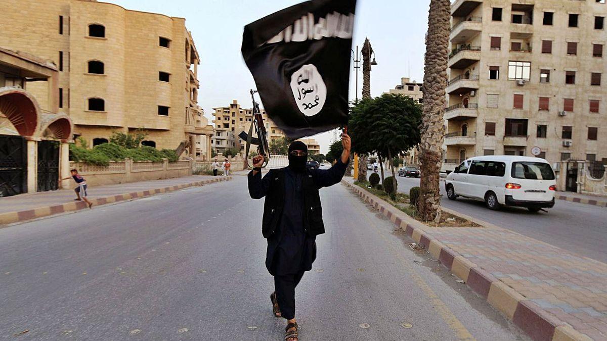 Un yihadista ondea una bandera del Estado Islámico en Raqqa (Siria)