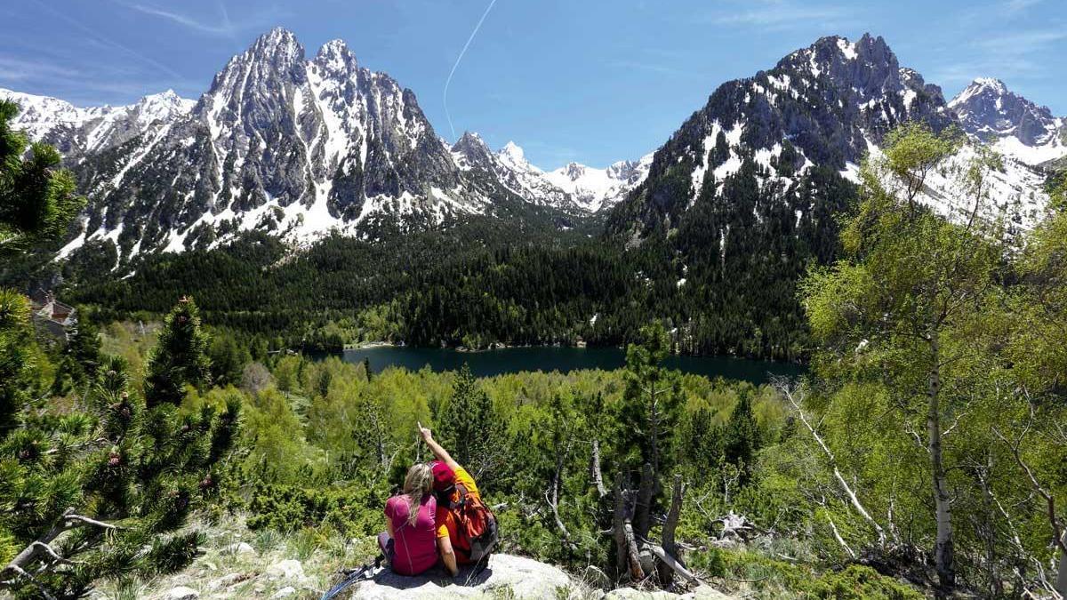 Una pareja de excursionistas admira Els Encantats, la montaña más emblemática de Aigüestortes.