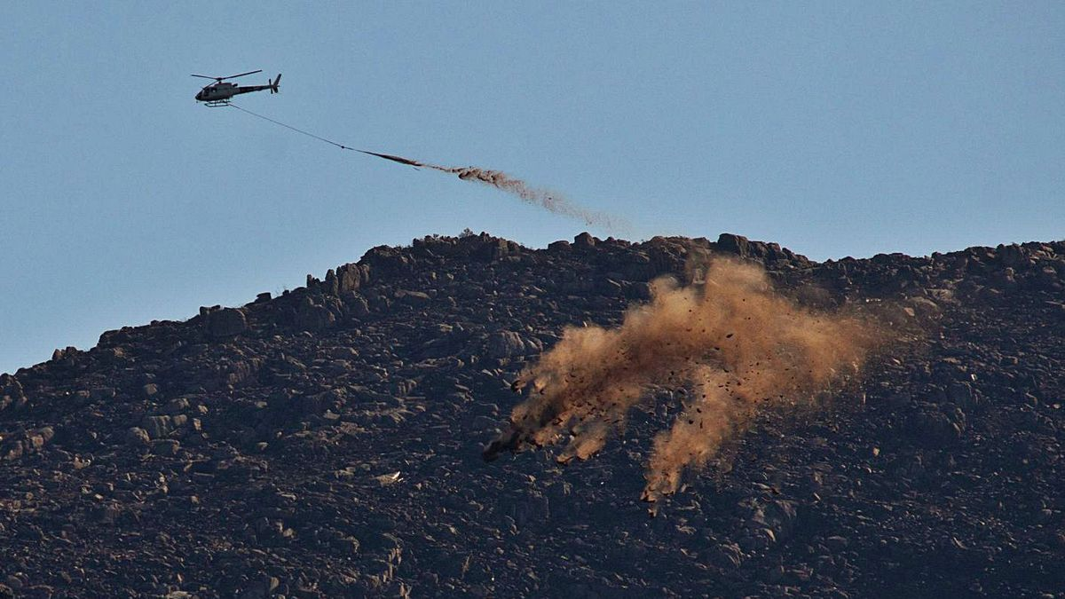 Un helicóptero esparce paja por los montes calcinados del Xurés, en Lobios.     // EFE/BRAIS LORENZO