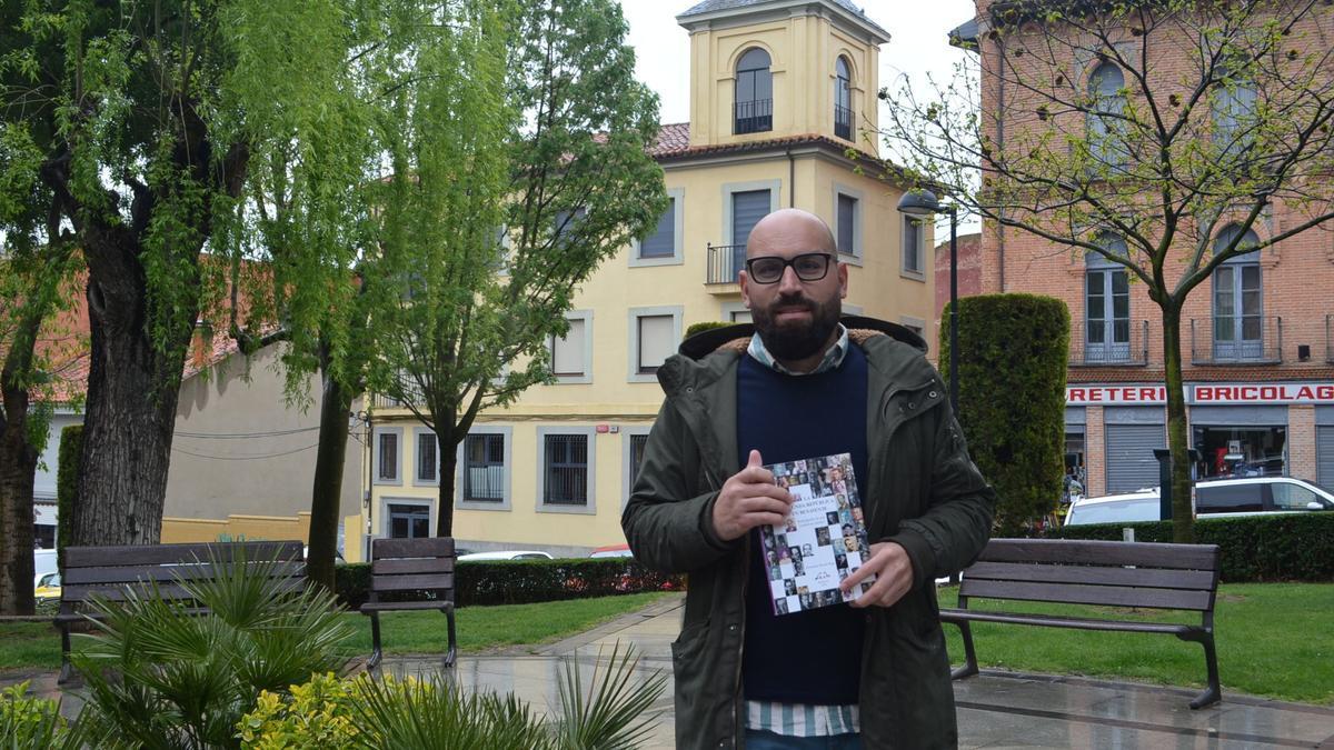 El benaventano Fernando Pernía muestra su nuevo libro, en la Plaza del Grano y al fondo el edificio de Correos. / E. P.