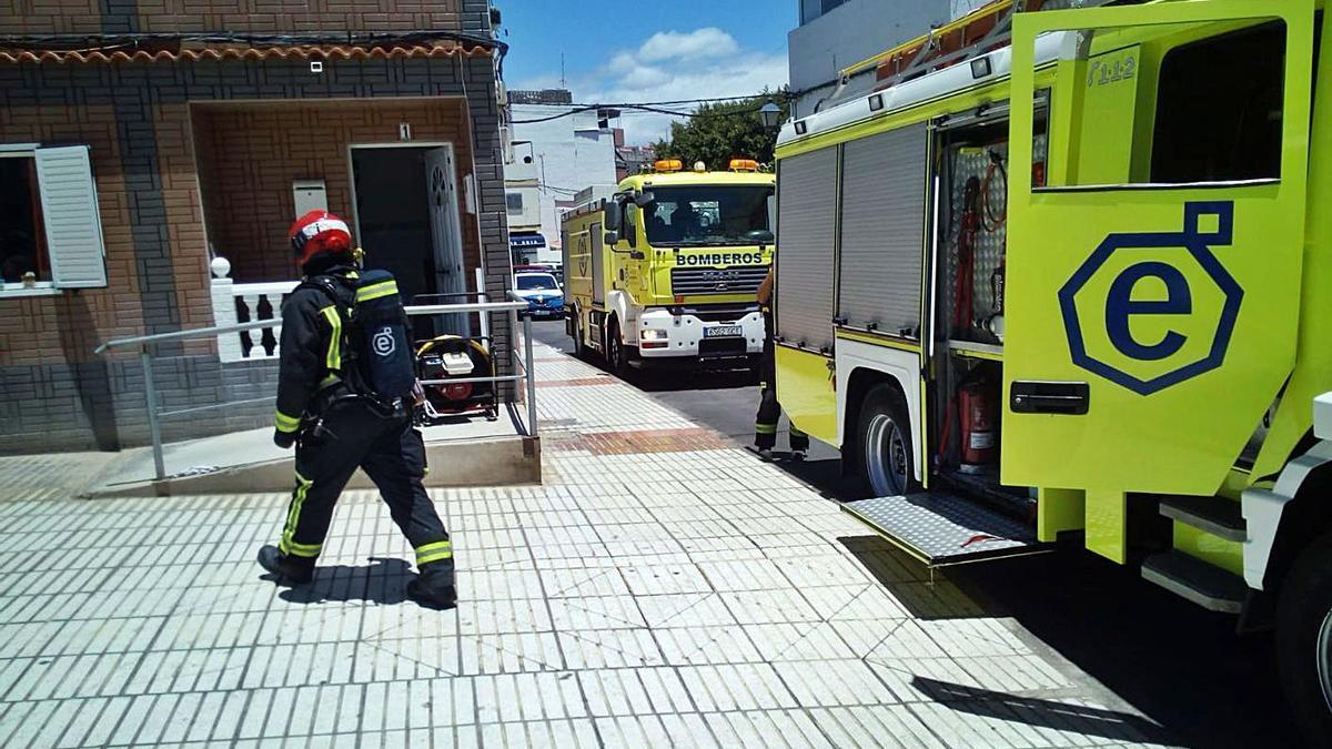 Uno de los bomberos se dirige a la puerta de la vivienda donde se produjo el incendio, ayer, en Arguineguín. | | LP/DLP