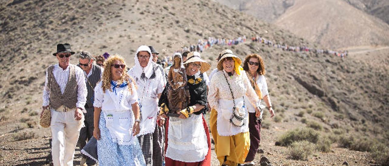 Un grupo de mujeres con la Virgen del Tanquito en brazos enfila hacia el santuario en la montaña.