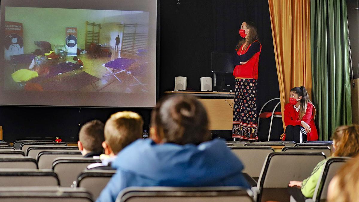 Escolares del colegio Rafael Altamira de Callosa miran atentos el vídeo con la intervención de Cruz Roja durante la DANA.