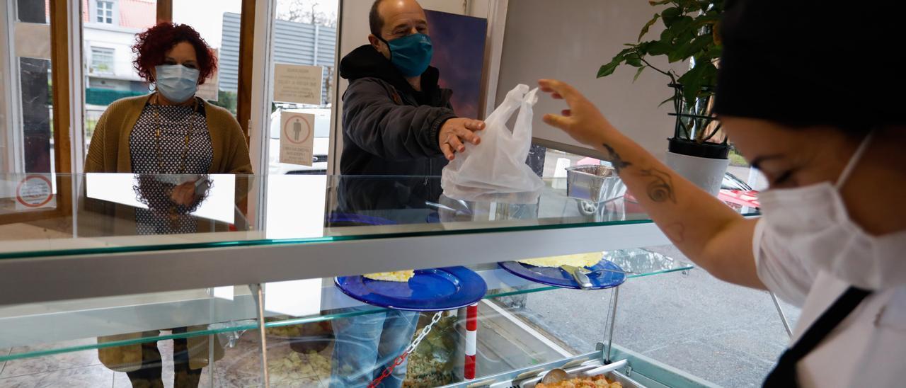 Silvia Fáez sirve una bolsa con comida a Miguel Macías, junto a la cocinera Covadonga Cancelas, ayer, en la tienda de Muros.