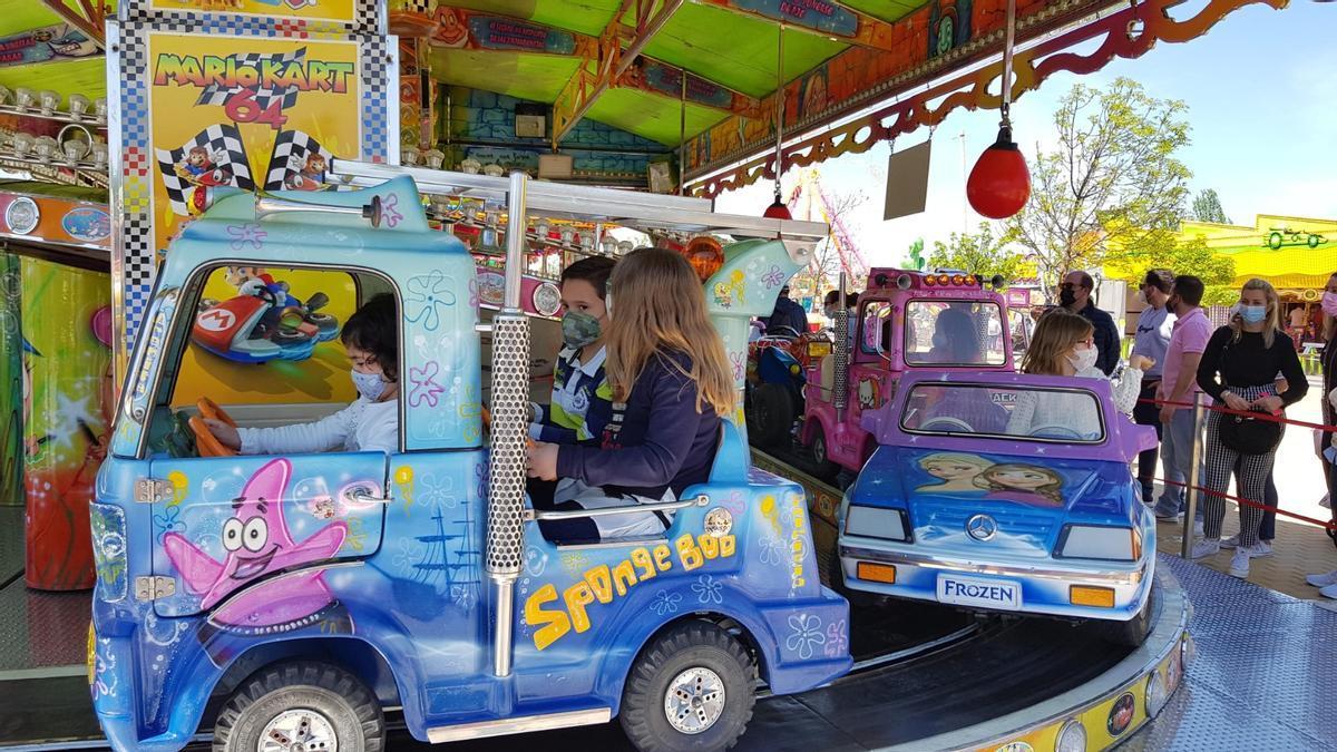 Varios niños se divierten en una de las atracciones de la Feria de la Primavera de Lucena.