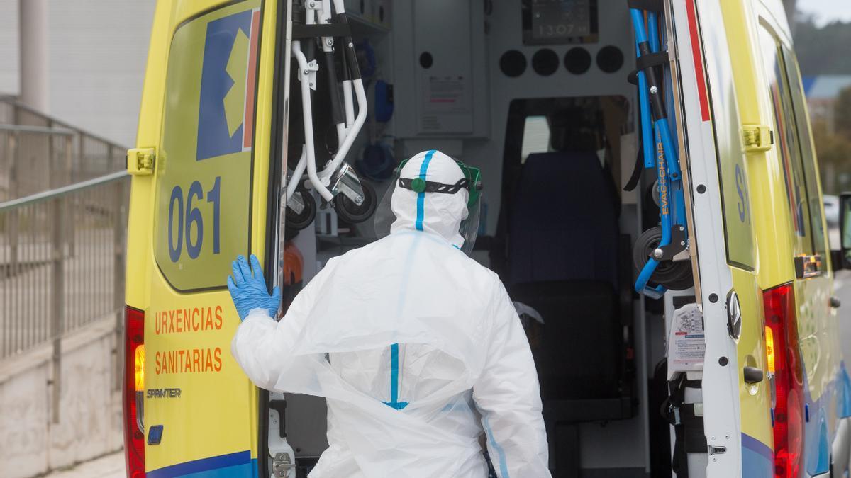 Un trabajador sanitario totalmente protegido cierra la puerta de una ambulancia tras recoger a un anciano de la residencia de ancianos de San Cibrao (Lugo).