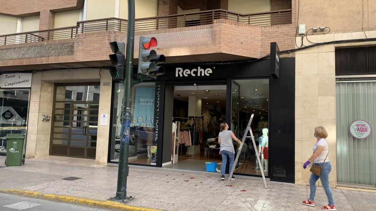 Las dependientas de una tienda preparan la apertura de hoy.