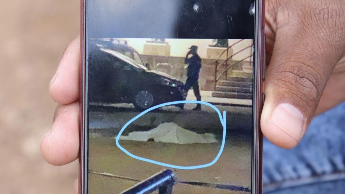 Un testigo muestra una fotografía del cadáver tendido en el suelo.