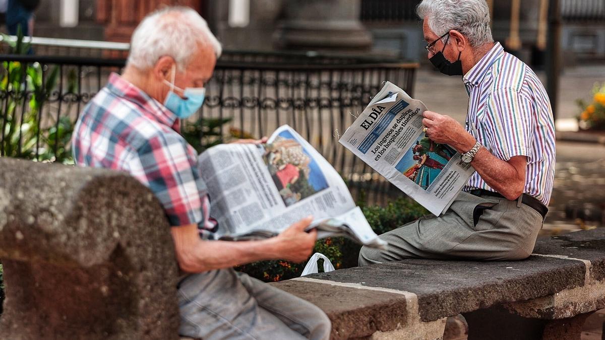 Dos hombres leen el periódico ataviados con mascarillas.