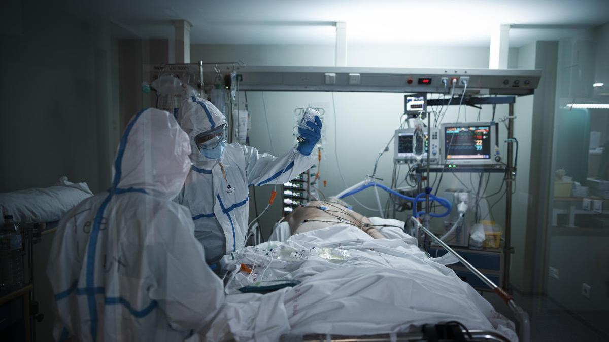 Dos sanitarios atienden a un paciente en la Unidad de Cuidados Intensivos del hospital del Rosell, en Cartagena.