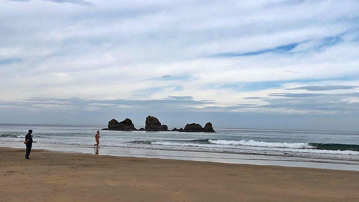 Un bañista y un paseante, ayer, en la playa de Aguilar.