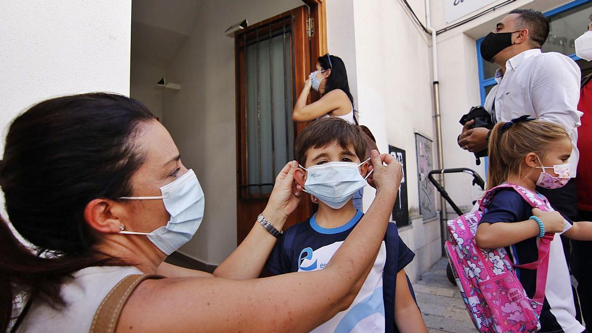 Una madre coloca la mascarilla a su hijo el primer día de clase en el colegio Santa Victoria.