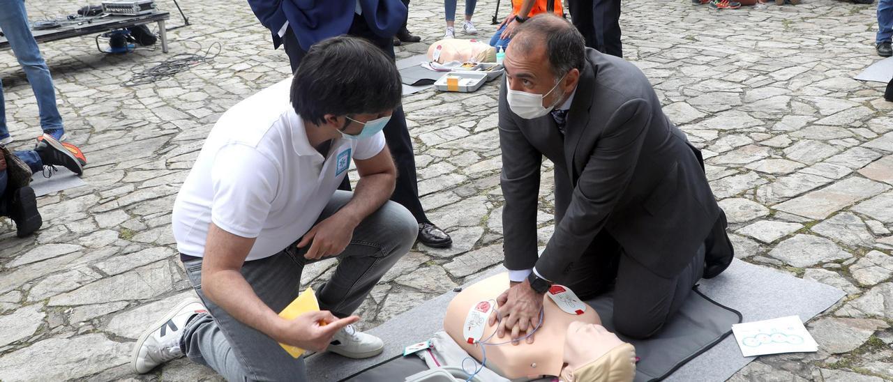 El conselleiro de Sanidade aplica maniobras de reanimación a un maniquí en un taller en la Plaza do Obradoiro.
