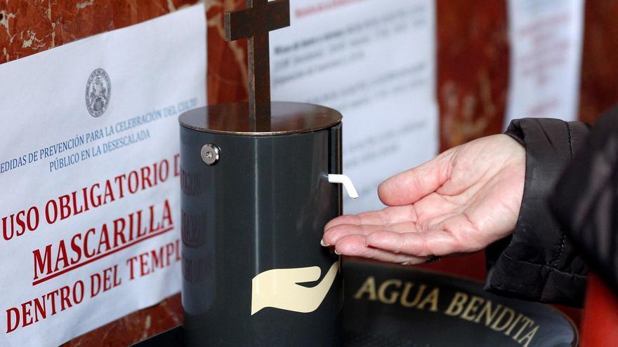 Una persona prueba el dispensador de agua bendita.