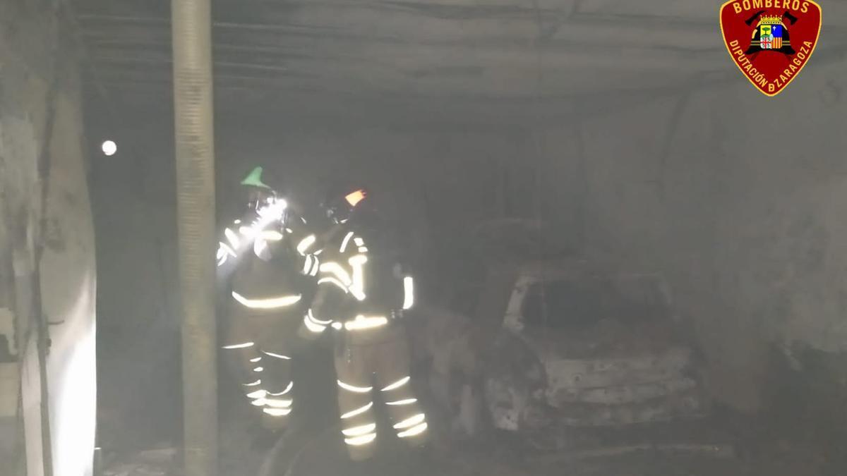 Los bomberos, junto al coche calcinado.