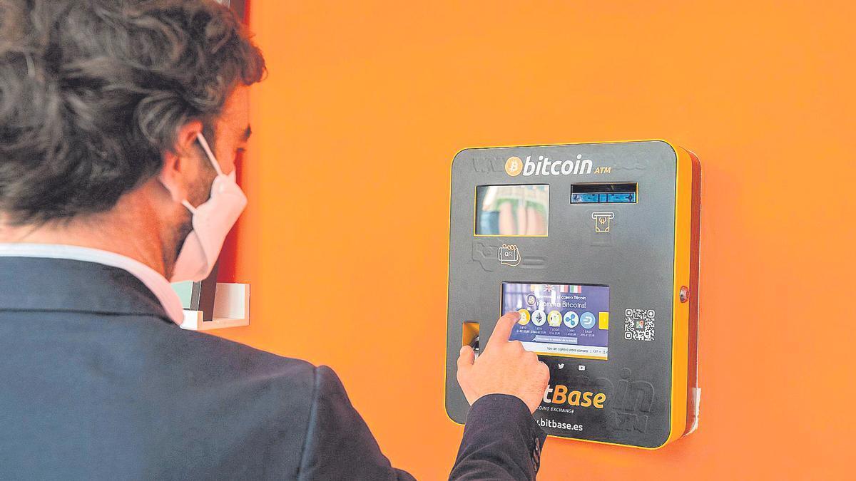 Un zaragozano introduce sus bitcoins en un cajero especializado disponible en la capital aragonesa