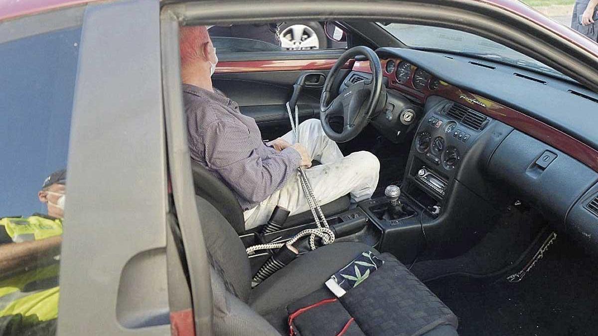 Puerta del vehículo sujeta con una cuerda al freno de mano al no encajar en el marco.