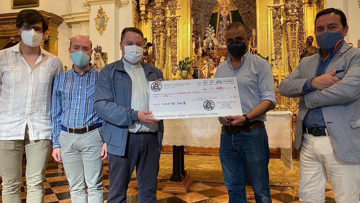 El presidente del Círculo de la Amistad de Cabra entrega el donativo al párroco.