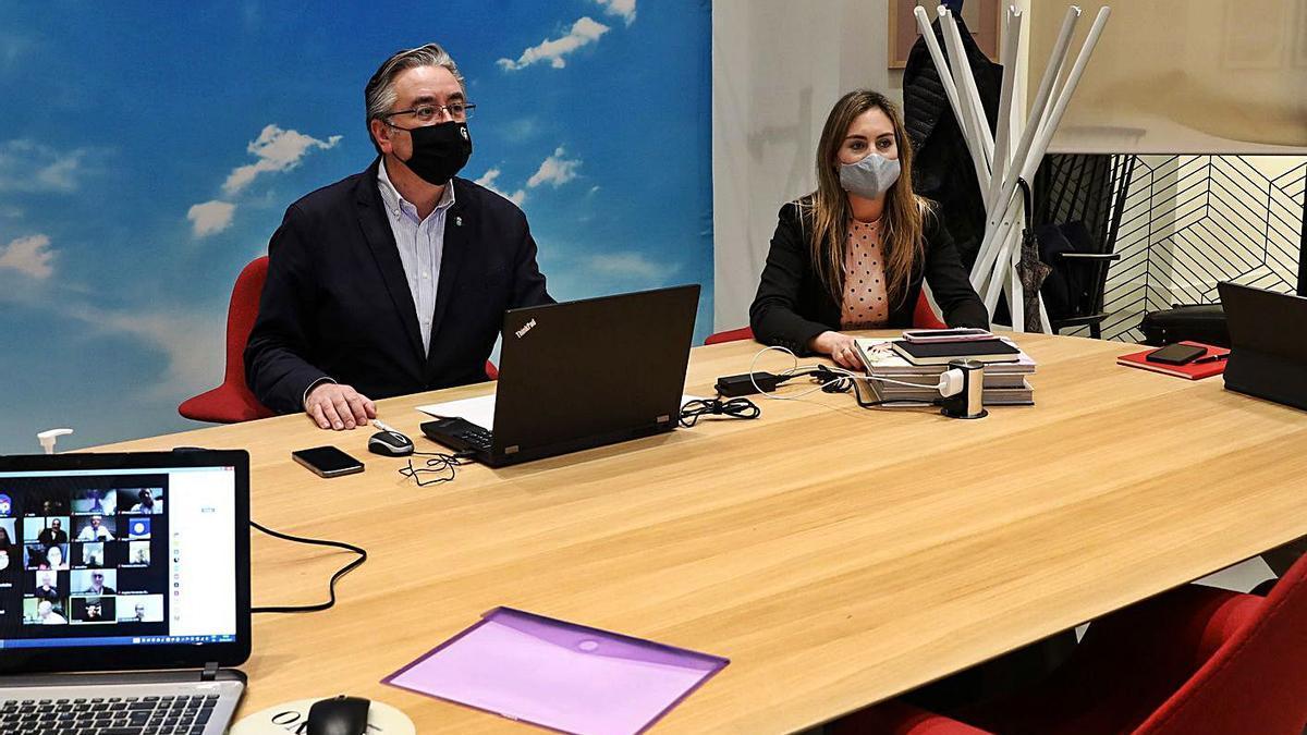 Pablo González y Cristina Villanueva, en un momento de la reunión telemática de la junta directiva local del PP de Gijón de ayer, que siguieron desde un despacho del antiguo Banco Urquijo.