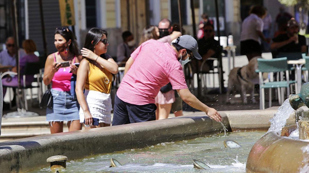 Un hombre se refresca ante las altas temperaturas en una fuente de la ciudad de València.