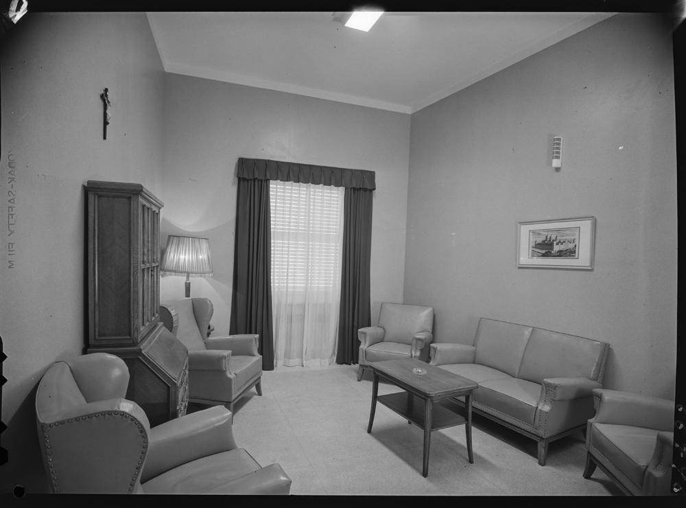 Sala de espera con sillones de piel, mobiliario de madera, crucifijo y cuadro en la pared.jpg