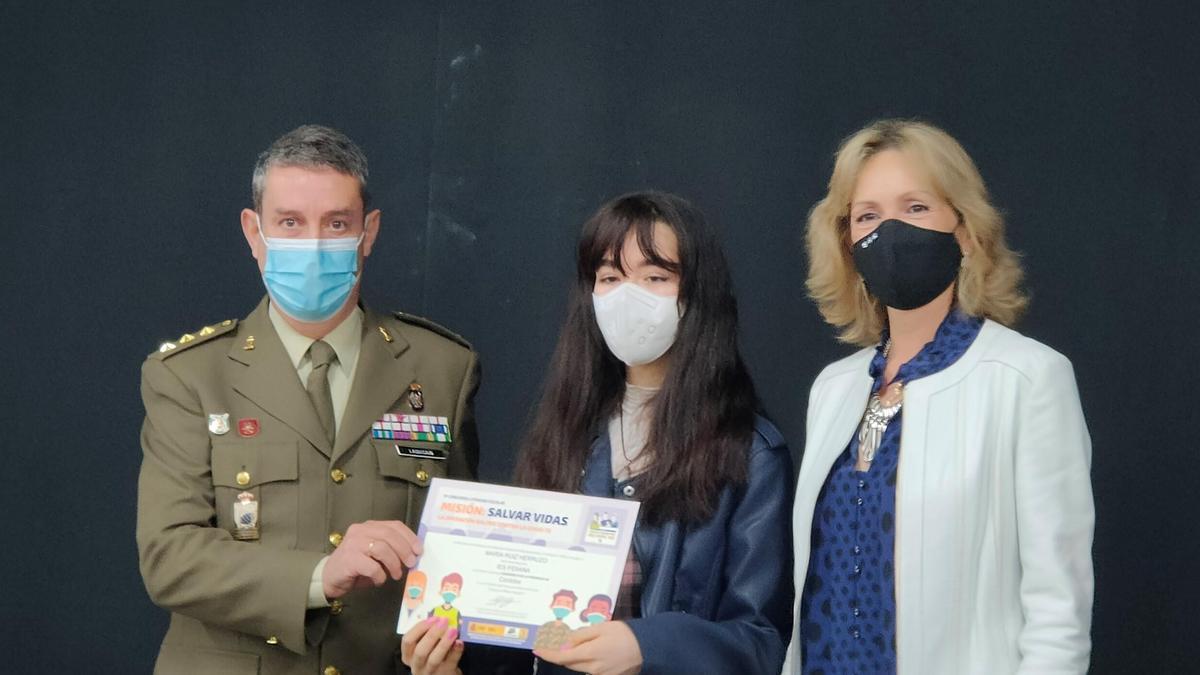 La alumna ganadora recibe el diploma que acredita su premio.