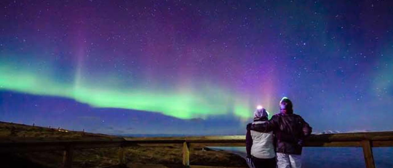 Una pareja disfruta de una aurora boreal.