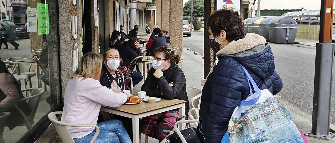 Varias personas disfrutan de unos cafés en una terraza de Arcade, ayer por la mañana