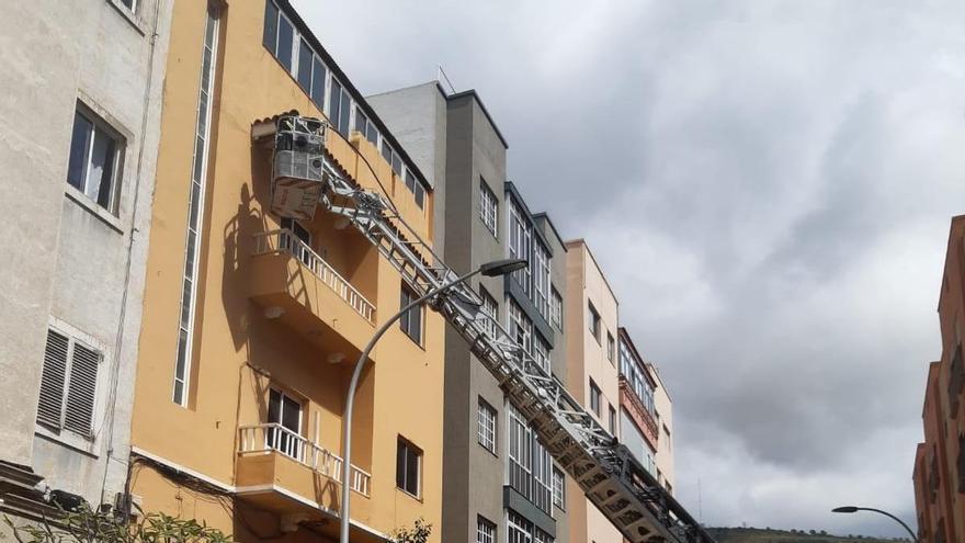 Los bomberos intervienen en la caída de cascotes de un edificio en Santa Cruz