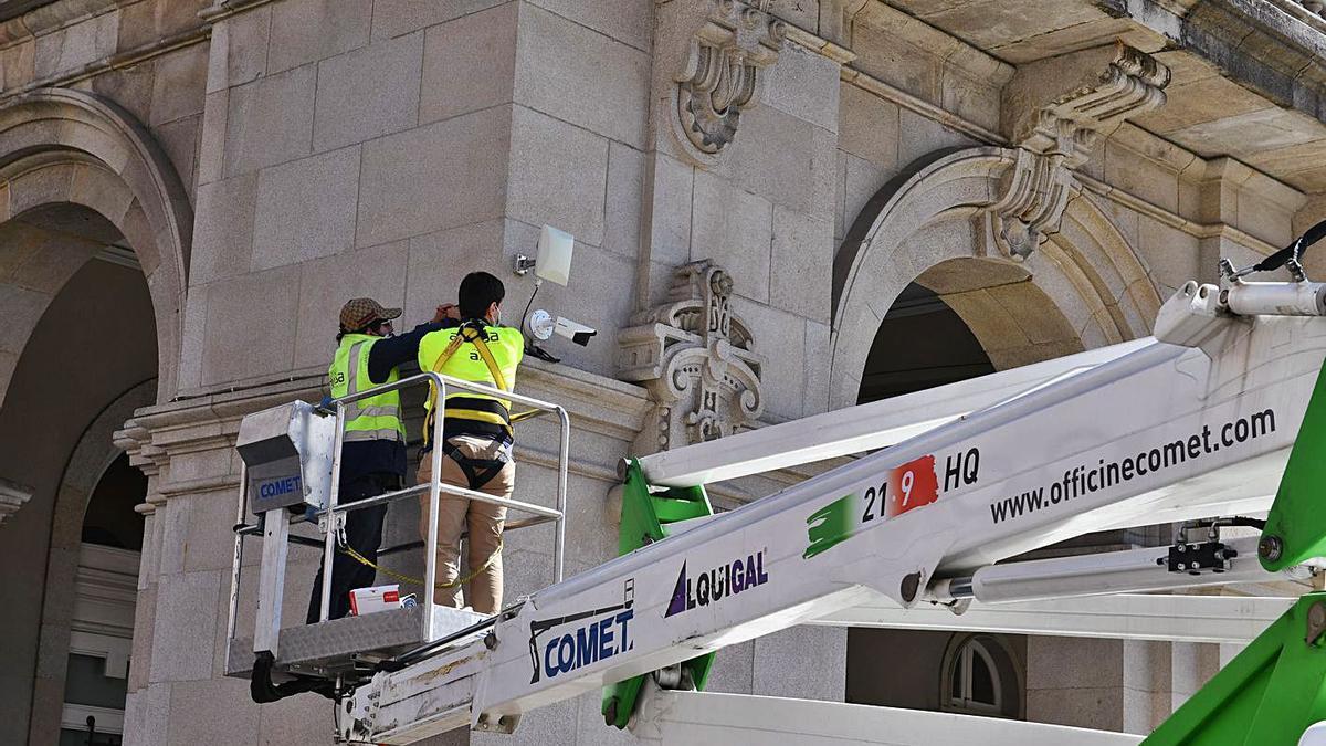 Dos operarios colocan una cámara de seguridad en el palacio municipal de María Pita.   | // VÍCTOR ECHAVE