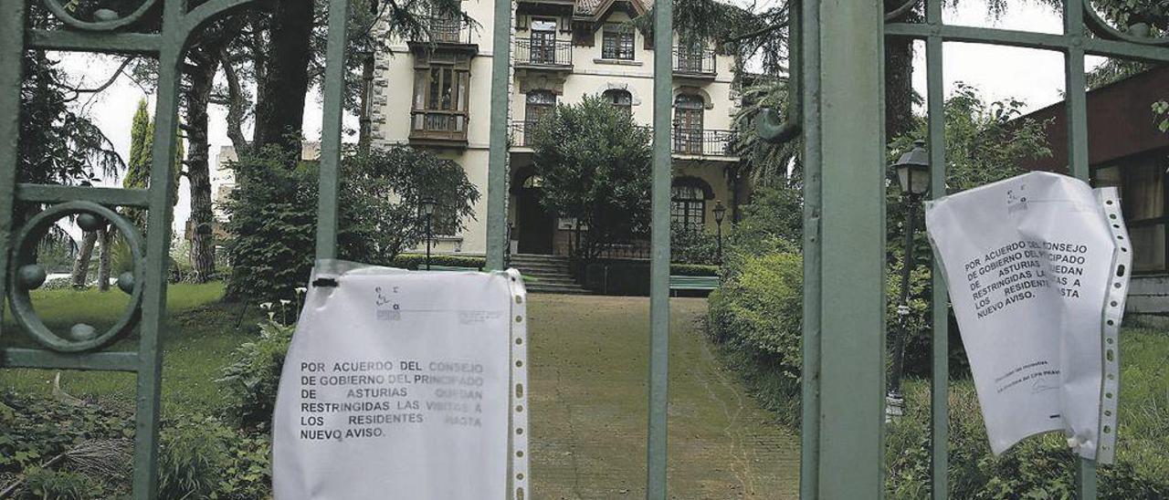 El acceso al recinto de la residencia y centro de día (en primer término) del ERA en Pravia, ayer, con el cartel que avisa de la restricción de las visitas.