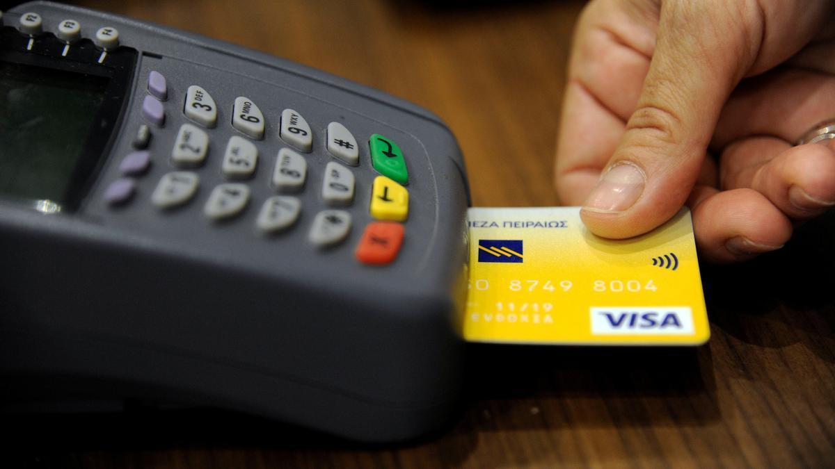 Una persona realizando un pago con tarjeta.