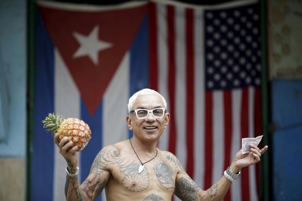 Zamora, un autónomo cubano de 55 años, posa frente a las banderas estadounidense y cubana después de la visita histórica de Obama a la isla.