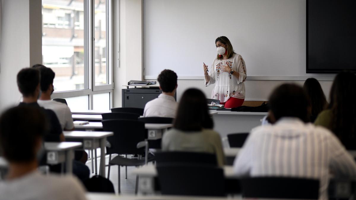Una profesora da clase con mascarilla a alumnos .