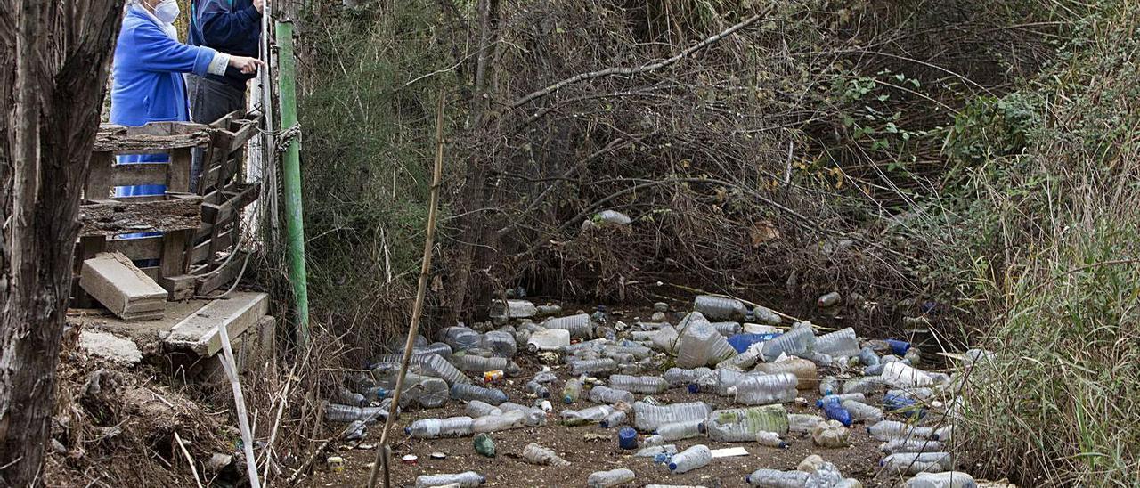 La afectada junto a un vecino, junto al muro caído, observan los residuos acumulados. | LEVANTE-EMV