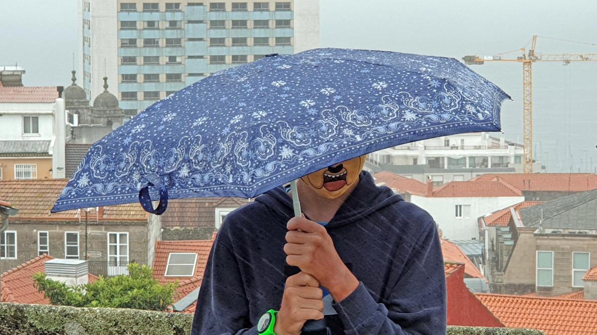 Una persona se protege de la lluvia en Vigo bajo un paraguas. // Marta G. Brea