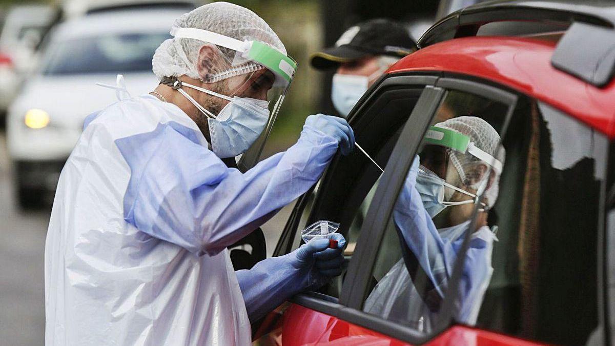 Un sanitario realiza una PCR a un paciente.