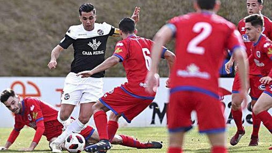Dani Hernández rodedado de jugadores del Numancia B.