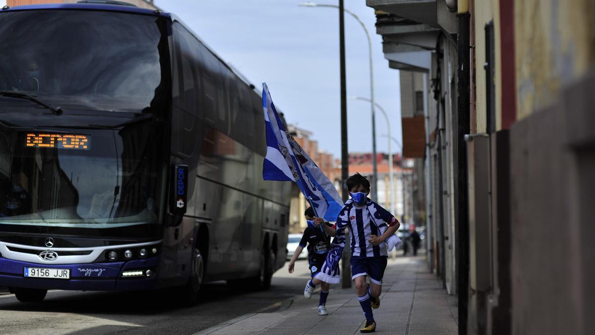 Dos niños corren al lado del bus del Deportivo el domingo en Luanco.