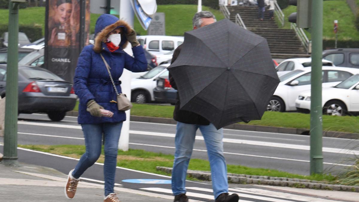 Varias personas en el paseo de A Coruña un día de tiempo inestable.