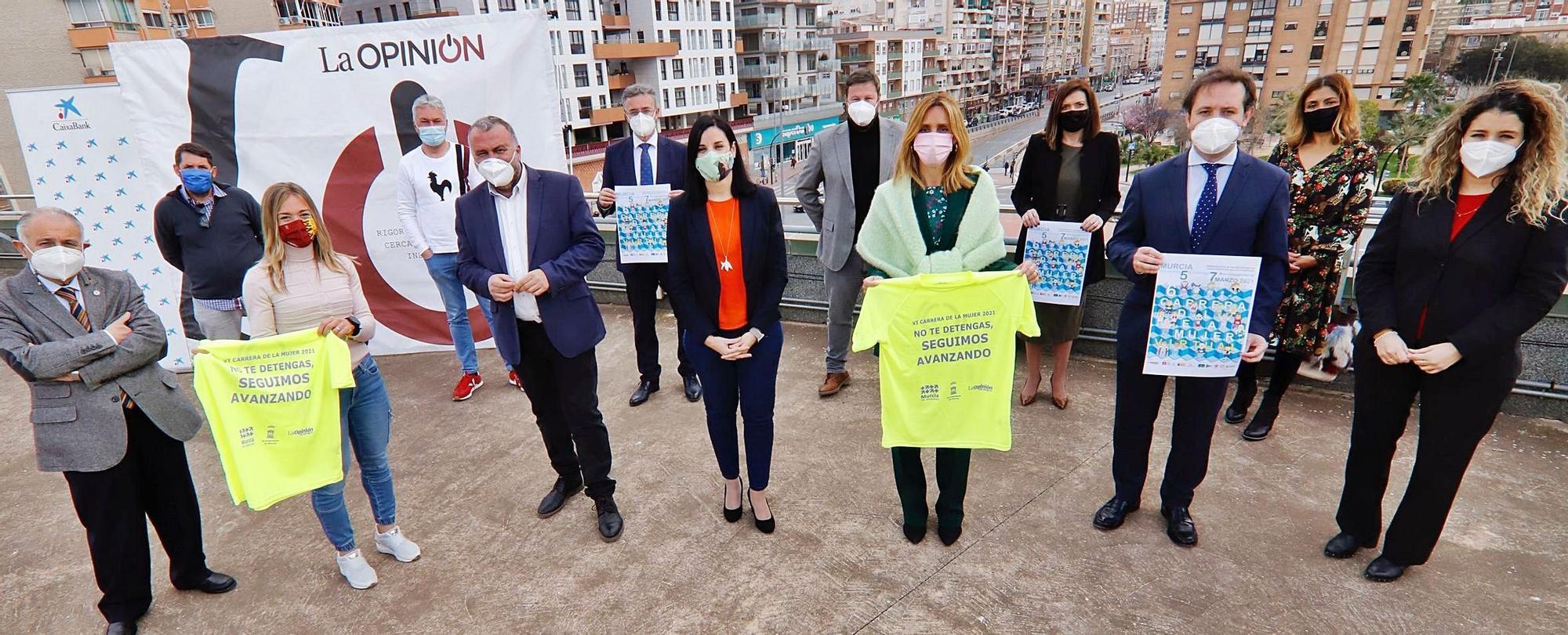 Patrocinadores y organizadores, ayer posando en el ático de La Opinión con el cartel de la carrera y la camiseta conmemorativa. | JUAN CARLOS CAVAL