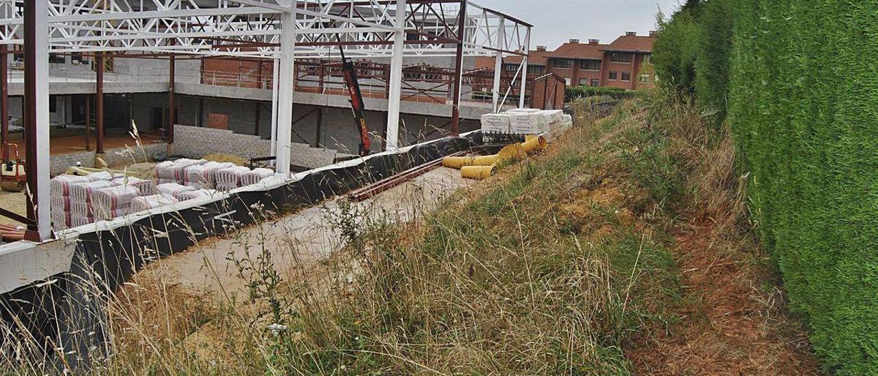 Las obras del instituto y una de las fincas afectadas, a la derecha.