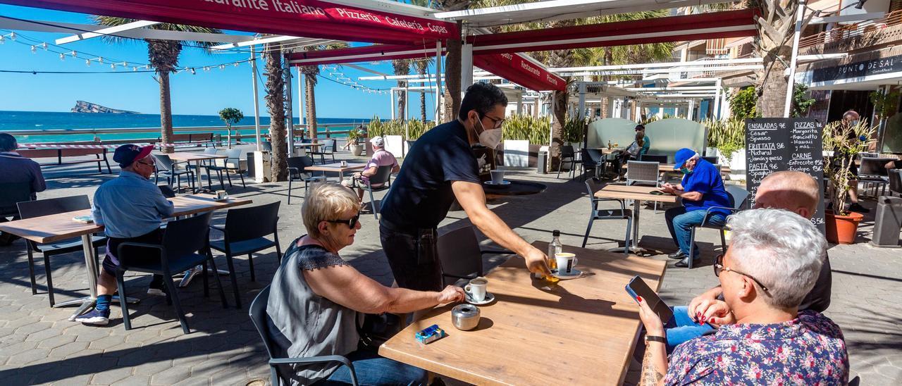 Un camarero atiende una terraza en Benidorm