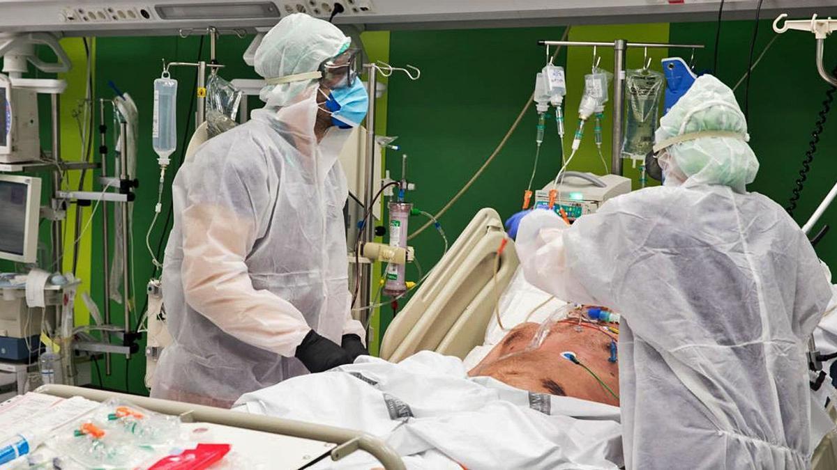 Dos sanitarios atendiendo a un paciente de covid
